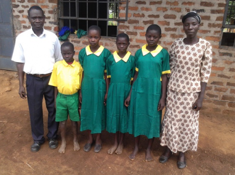 Uniform beneficiaries at Kotoo Primary School, with Child-to-Child Club teacher & Community Health Worker
